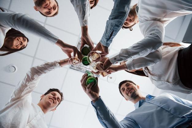 Foto dal basso. bussare gli occhiali in ufficio. festeggiamo il successo