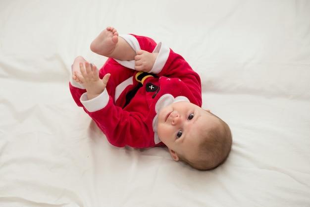 Foto del bambino che si trova sulla schiena indossando il costume di santa sul lenzuolo