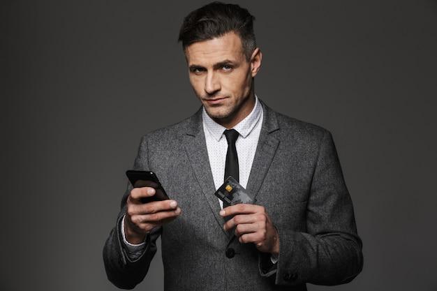 Foto del capo azienda in abbigliamento formale che paga online con smartphone e carta di credito, isolato sopra il muro grigio