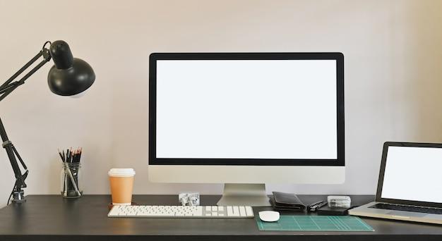 Foto del computer bianco dello schermo in bianco e del computer portatile bianco dello schermo in bianco che mettono insieme sulla tavola compreso la lampada, la tazza di caffè, il supporto della matita del topo e l'attrezzatura personale. concetto di scrivania moderna.