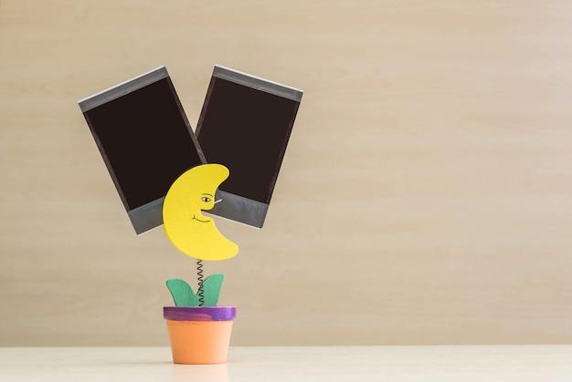 Foto del morsetto del primo piano nella forma della luna gialla in vaso da fiori con il film in bianco nero