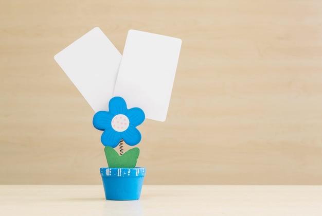 Foto del morsetto del primo piano nella forma di forma del fiore blu in vaso da fiori con libro bianco nero