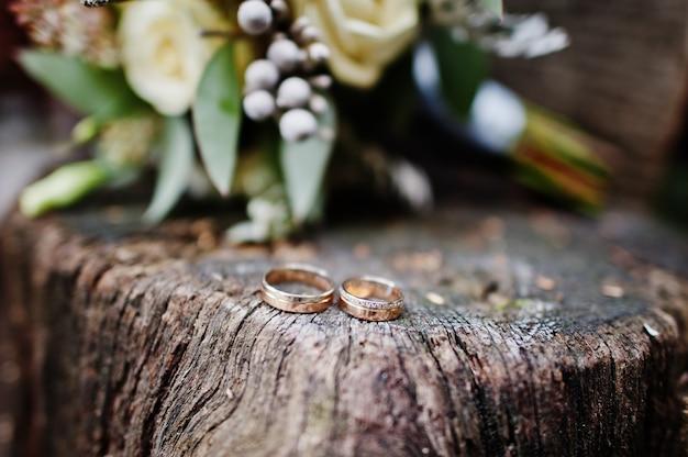 Foto del primo piano degli anelli dorati sul ceppo di legno.
