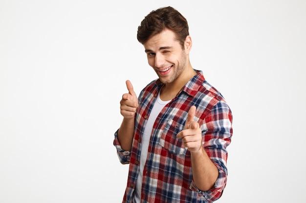 Foto del primo piano del giovane rasato allegro in camicia a quadretti che indica con due dita