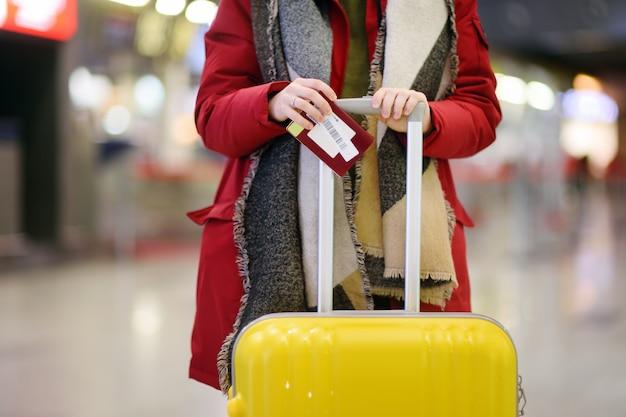 Foto del primo piano del passaporto della tenuta della donna e della carta d'imbarco all'aeroporto internazionale