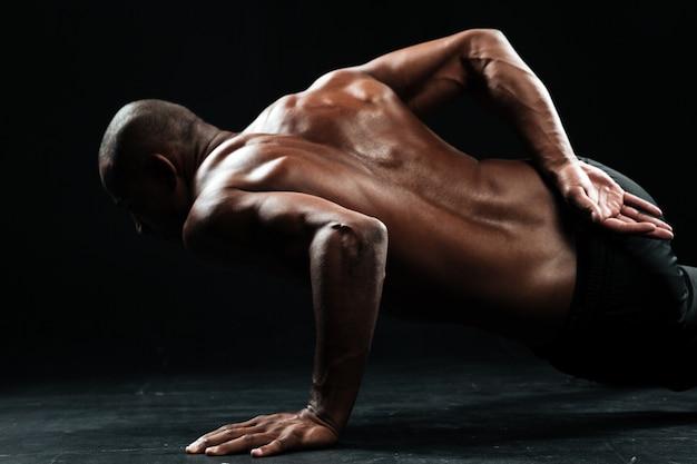 Foto del primo piano dell'atleta maschio afroamericano che fa esercizio con una mano di flessioni