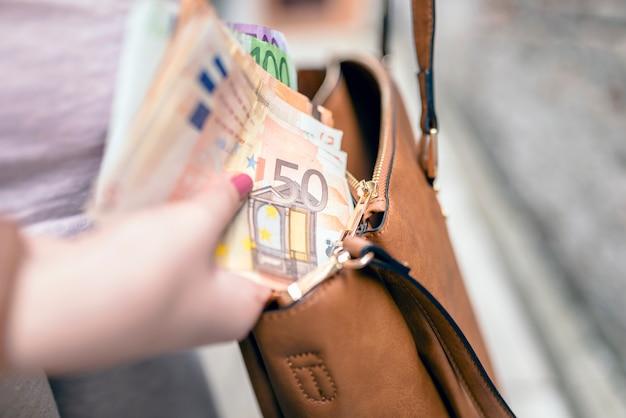 Foto del primo piano della donna alla moda che prende soldi fuori la borsa. la donna si prepara a pagare