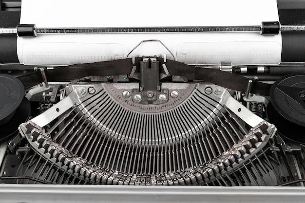 Foto del primo piano della macchina da scrivere d'annata con lo strato di carta vuoto