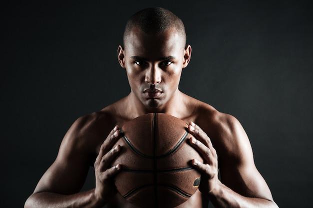 Foto del primo piano della palla afroamericana della tenuta del giocatore di pallacanestro con due mani
