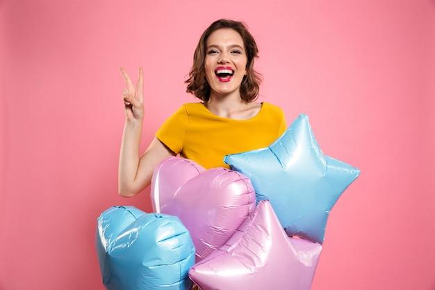 Foto del primo piano della ragazza di buon compleanno con le labbra rosse che tengono i palloni, mostrando il gesto di pace,