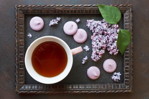 Foto del primo piano della tazza di tè con i maccheroni e bello lillà fresco nel telaio sulla tavola nera
