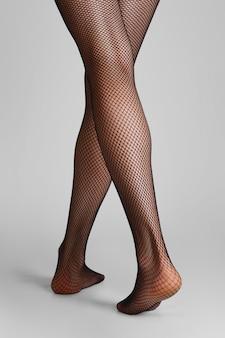 Foto del primo piano delle gambe femminili esili lunghe in calzamaglia a rete nere. vista posteriore, vai via