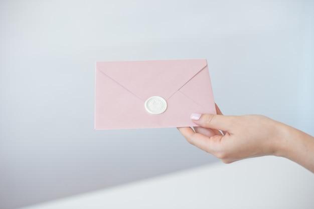 Foto del primo piano delle mani femminili che tengono la busta dell'invito con un sigillo di cera, buono regalo, cartolina, carta dell'invito di nozze.