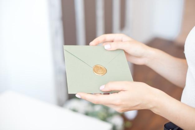 Foto del primo piano delle mani femminili che tengono la busta dell'invito con un sigillo di cera, un buono regalo, una cartolina, una carta dell'invito di nozze.