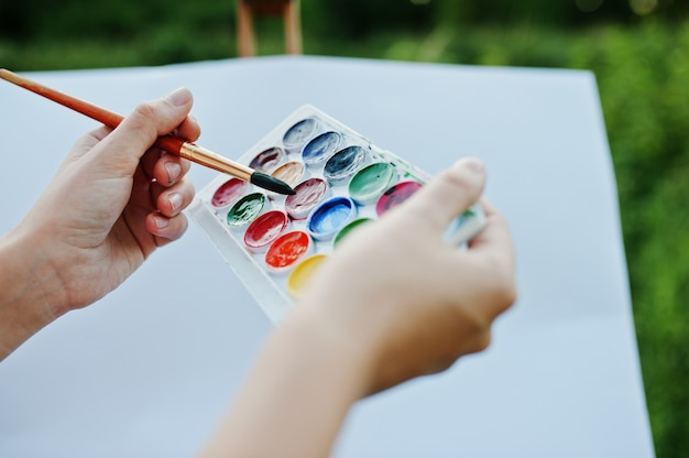 Foto del primo piano delle mani femminili che tengono le pitture dell'acquerello e una spazzola mentre dipingendo in natura.