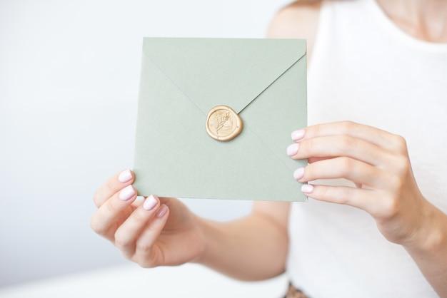 Foto del primo piano delle mani femminili che tengono una busta d'argento dell'invito con un sigillo di cera, un buono regalo, una cartolina, una carta dell'invito di nozze.