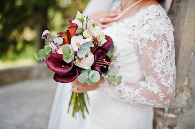 Foto del primo piano di bello mazzo di nozze in mani della sposa.