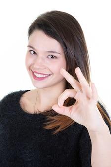 Foto del primo piano di giovane donna castana divertente in maglione nero che mostra gesto giusto