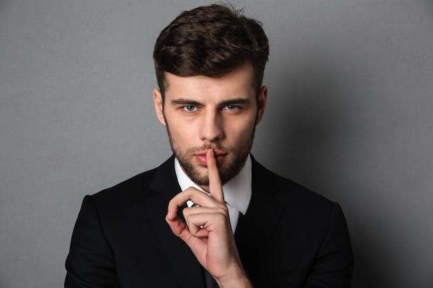 Foto del primo piano di giovane uomo bello in vestito nero che mostra gesto di silenzio,
