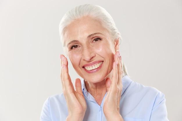 Foto del primo piano di risata della donna senior dai capelli grigi