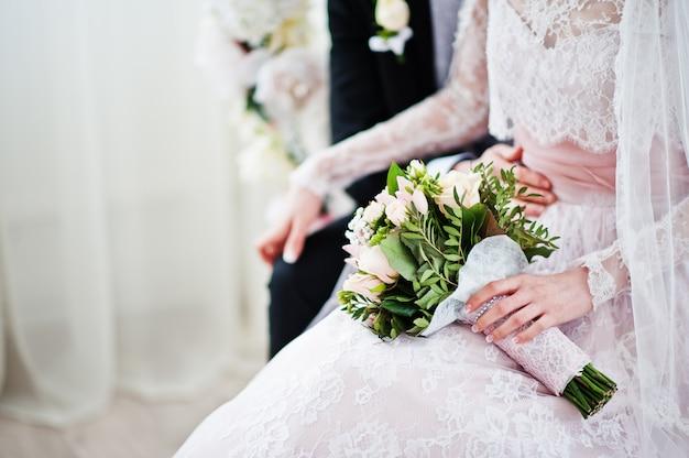 Foto del primo piano di un mazzo in mani della sposa.