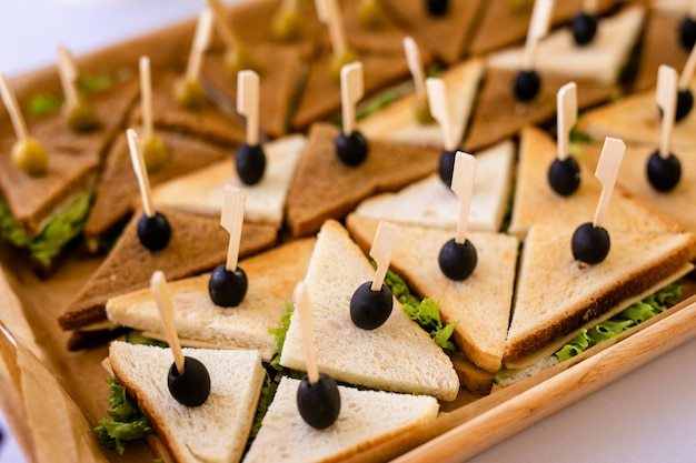 Foto del primo piano di un panino di club. panino con prosciutto, prosciutto, insalata, verdure, lattuga e olive su un pane di segale fresco a fette