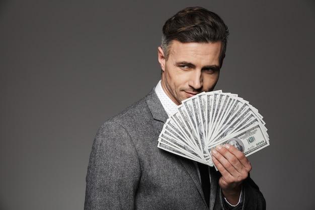 Foto del ragazzo fortunato anni '30 in giacca e cravatta che dimostra il premio in denaro in banconote da un dollaro e, isolato sopra il muro grigio