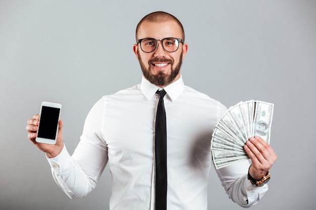 Foto del riuscito uomo 30s in vetri e legame che tiene telefono cellulare e fan delle banconote in dollari, isolato sopra la parete grigia