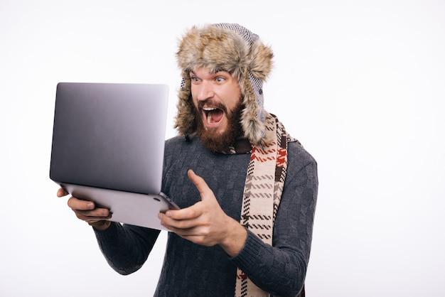 Foto del tipo barbuto che indossa i vestiti caldi di inverno, tenendo computer portatile e sembrando schocked, controllando fondo isolato