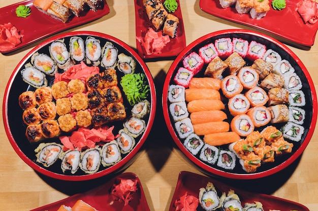 Foto del vassoio di sushi fresco di maki con molta varietà. messa a fuoco selettiva al centro del piatto.