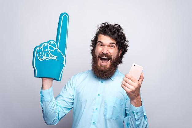 Foto dell'uomo barbuto stupito in camicia blu che tiene il telefono e il guanto della schiuma della ventola