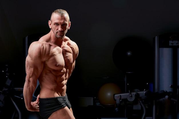 Foto dell'uomo con fisico muscoloso su fondo nero.