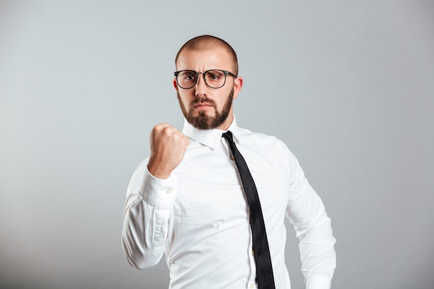 Foto dell'uomo d'affari utile in camicia bianca ed occhiali che gesturing pugno sulla fortezza di significato della macchina fotografica, isolata sopra la parete grigia