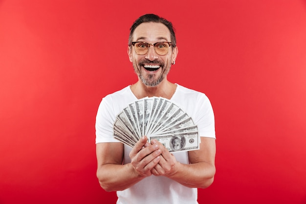 Foto dell'uomo eccitato e ricco in maglietta bianca casuale che sorride e che dimostra fan di soldi in banconote del dollaro che tengono in mano, isolato sopra la parete rossa