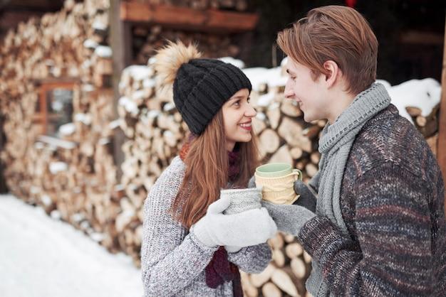 Foto dell'uomo felice e della donna graziosa con le tazze all'aperto nell'inverno. vacanze invernali e vacanze. le coppie di natale dell'uomo e della donna felici bevono il vino caldo. coppia innamorata