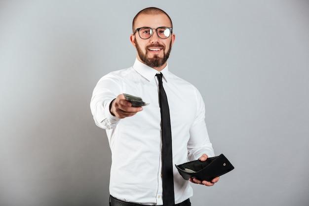 Foto dell'uomo maturo in vetri e vestito che dà i contanti del dollaro dei soldi sulla macchina fotografica dal portafoglio, isolata sopra la parete grigia