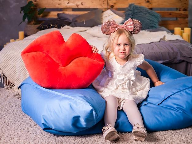 Foto della bambina bionda graziosa in vestito bianco che tiene le grandi labbra rosse