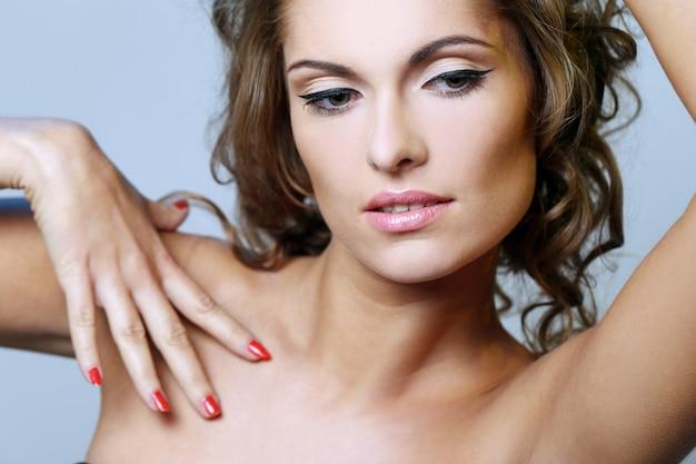 Foto della bella ragazza e lei tocca la sua pelle, guarda in basso