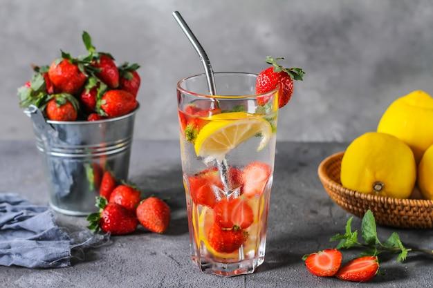 Foto della bevanda fredda ghiacciata di estate rinfrescante. acque infuse alla fragola. acqua minerale con fragole fresche limone con uno sfondo grigio. acqua disintossicante con limone e fragola. copia spazio.