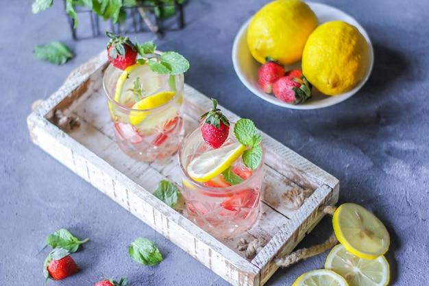 Foto della bevanda fredda ghiacciata di estate rinfrescante con la limonata della menta del limone della fragola in vetro. acqua minerale con fragole fresche e limone. acqua disintossicante con menta e limone e fragola. copia spazio. scatola di legno