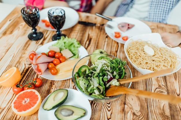 Foto della cena romantica a casa, coppia che produce maccheroni e salata