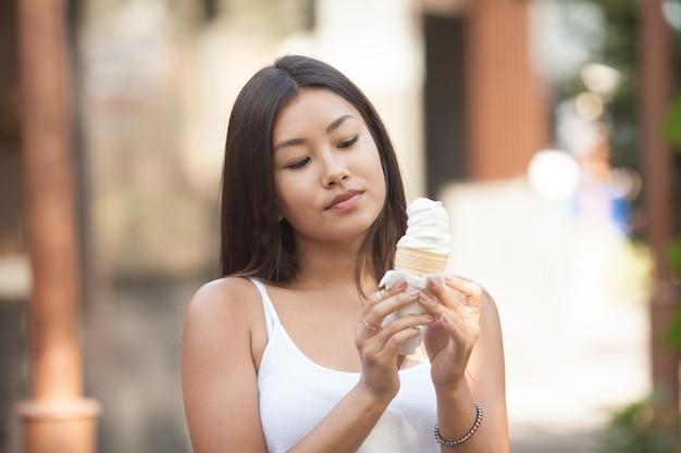 Foto della donna asiatica che mangia il gelato e supporto nella stagione calda. la felicità emotiva. focus sul viso.