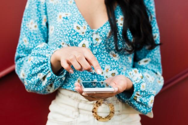 Foto della donna che usando e che indica al suo telefono