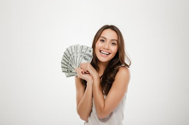 Foto della donna sorridente fortunata con capelli lunghi che vincono un sacco di banconote in dollari dei soldi, essendo ricca e felice sopra la parete bianca