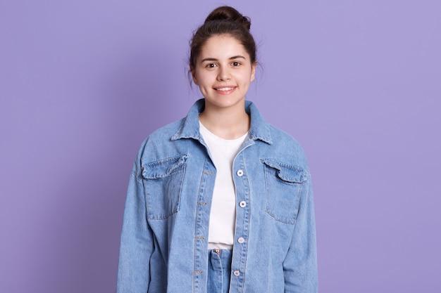 Foto della donna splendida abbastanza allegra, ragazza castana che indossa camicia bianca e posa del rivestimento del denim isolata sopra la parete lilla