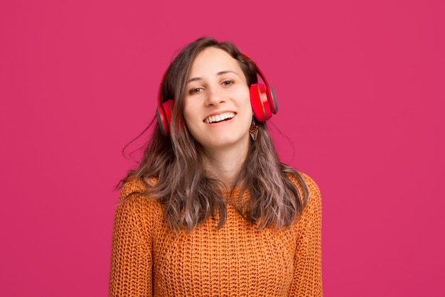 Foto della giovane donna allegra che porta maglione giallo e musica d'ascolto alle cuffie