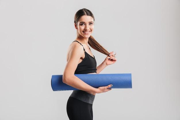 Foto della giovane donna esile in stuoia di yoga della tenuta della tuta sportiva e guardare, isolata sopra la parete grigia
