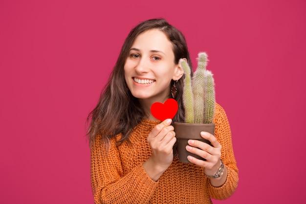 Foto della pianta felice del cactus della tenuta della donna e della forma rossa del cuore