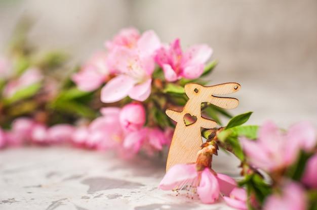 Foto della primavera di un albero sbocciante del primo piano e dei coniglietti e spazio della copia.