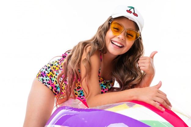 Foto della ragazza affascinante in un costume da bagno su una priorità bassa bianca